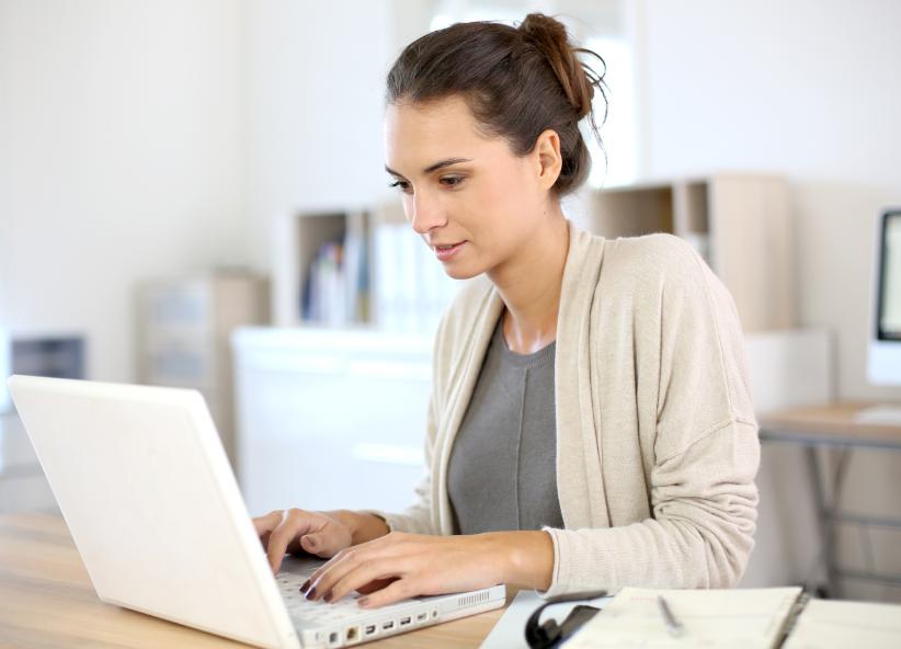 Mulher concentrada enquanto usa o notebook.