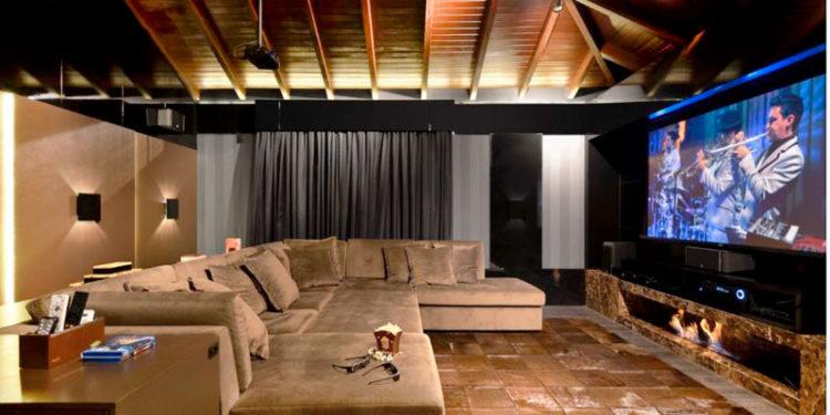 Cinema em casa com poltronas reclináveis e uma tela gigante.