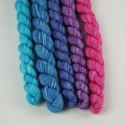 image of five 20g skeins of yarn, going from left to right is an ombre from bright turquoise on the left to purple in the middle and bright magenta on the right.