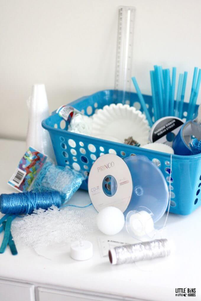 A blue basket filled with white and blue tinkering supplies like yarn, old cds, rubber bands, straws, etc.