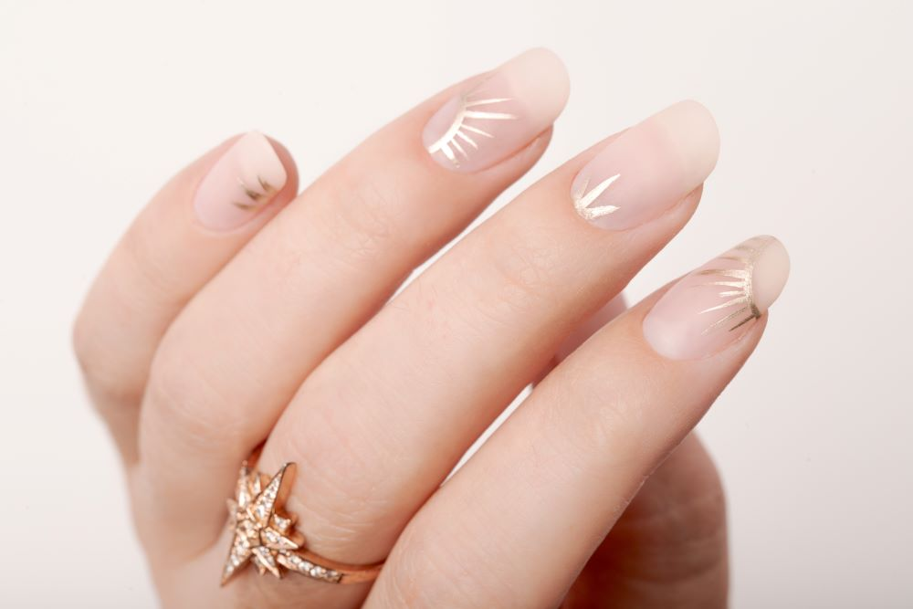 nude matte nails with gold metallic sunbursts