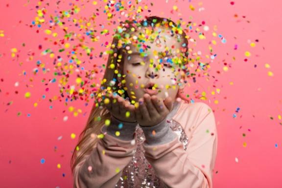 Niña feliz celebrando sopla confeti multicolor   Foto Premium