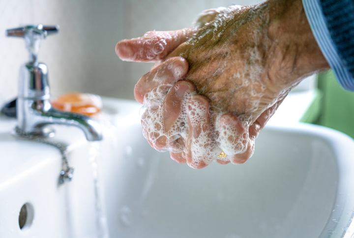 a closeup shot of a pair of older hands covered in soap in the middle of washing