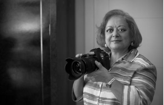 Foto en blanco y negro de una persona con una cámara fotográfica  Descripción generada automáticamente