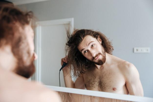 Man drying hair with hairdryer at home  hair care tips