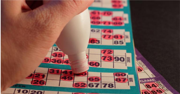 Rotulador rojo tachando varios números en un cartón de bingo.