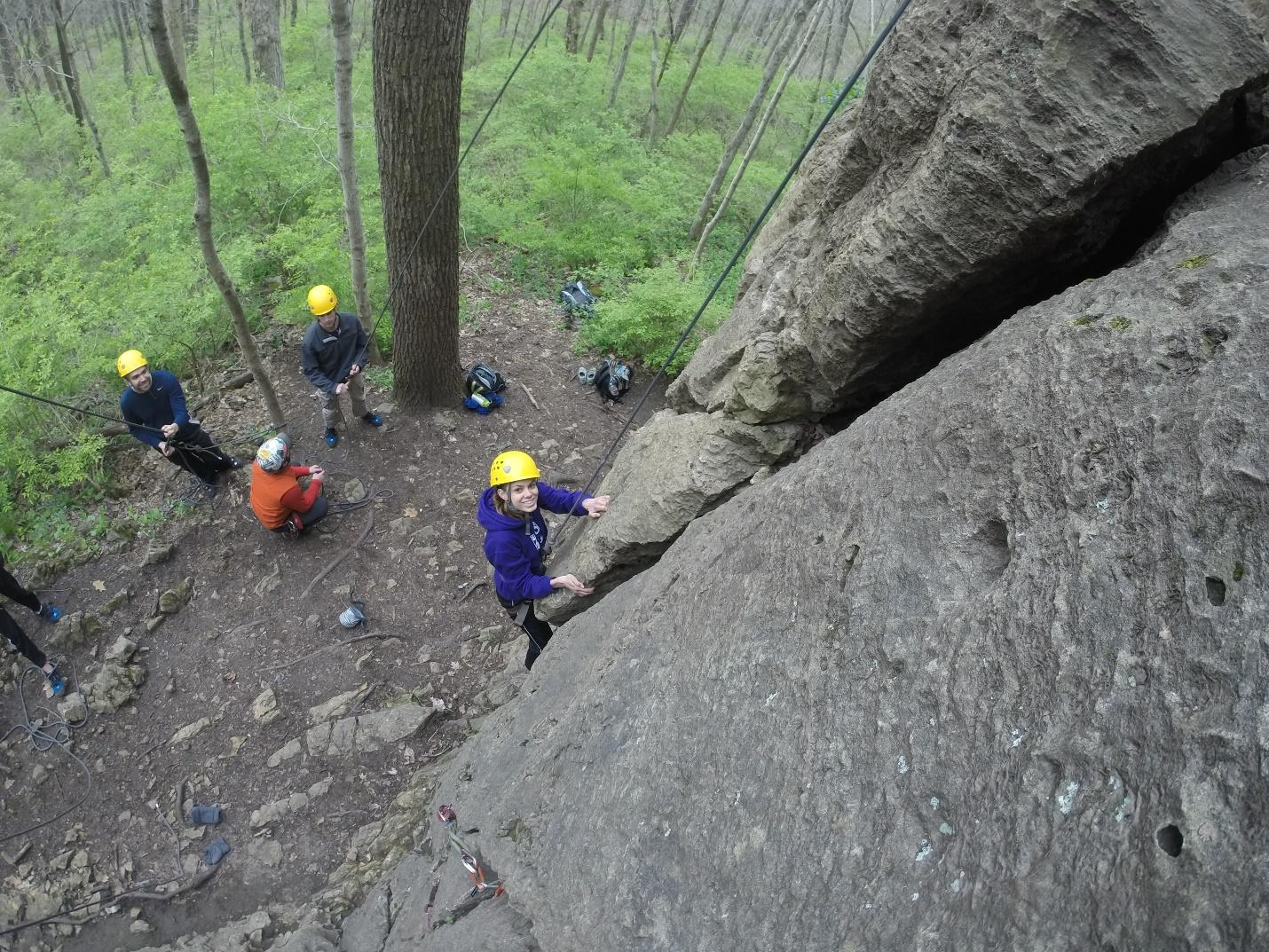 students climbing a rock