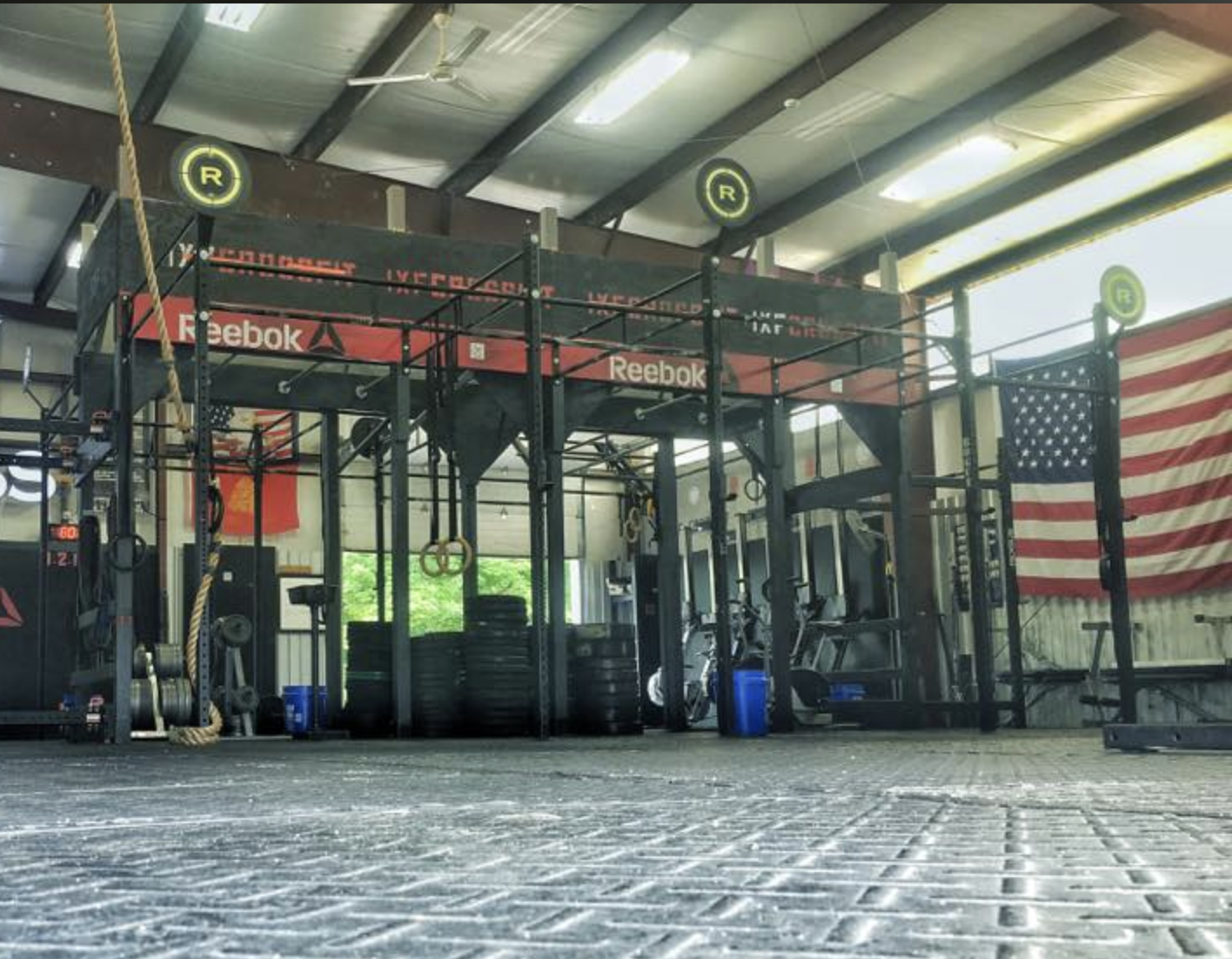 image of a gym with pull up racks and black mat floor