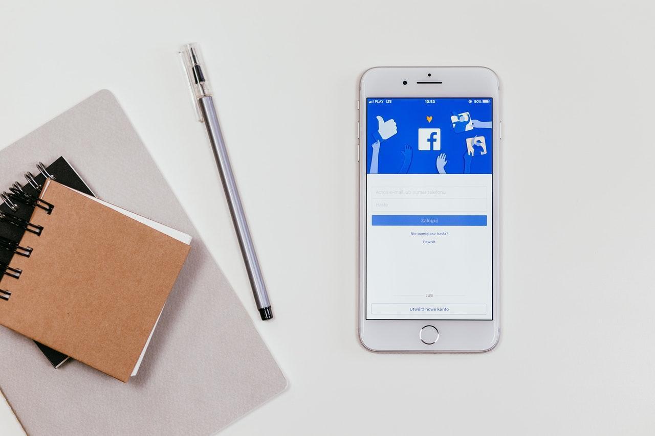 Facebook ouvert sur un téléphone portable avec des stylos et de la papeterie sur une table blanche