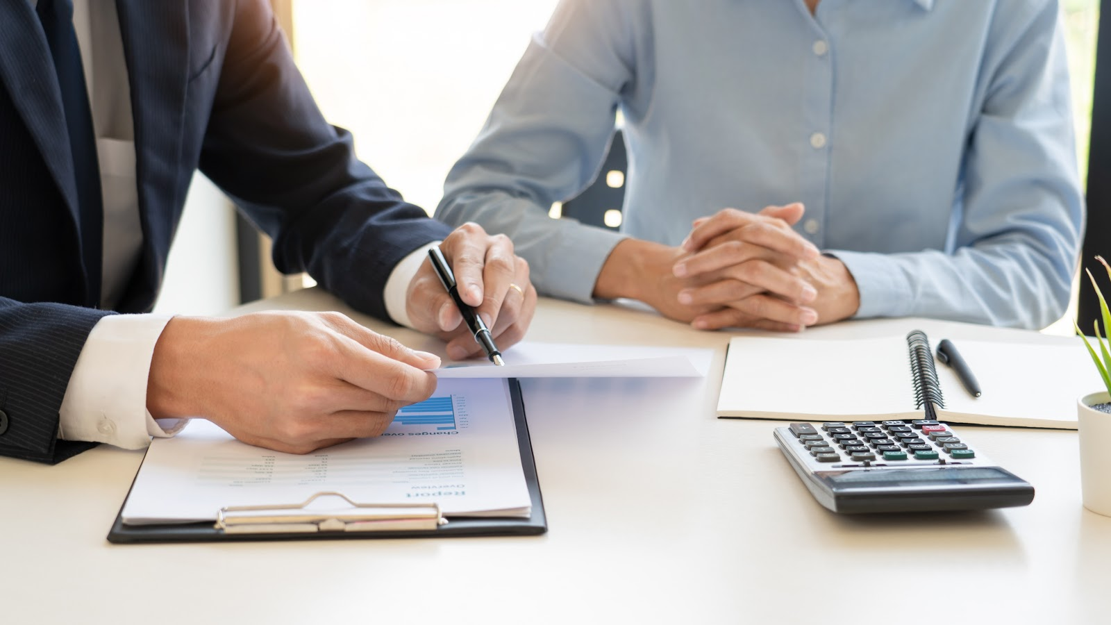 stocks that pay monthly dividends: Man holding a pen and paper while his colleague sits beside him