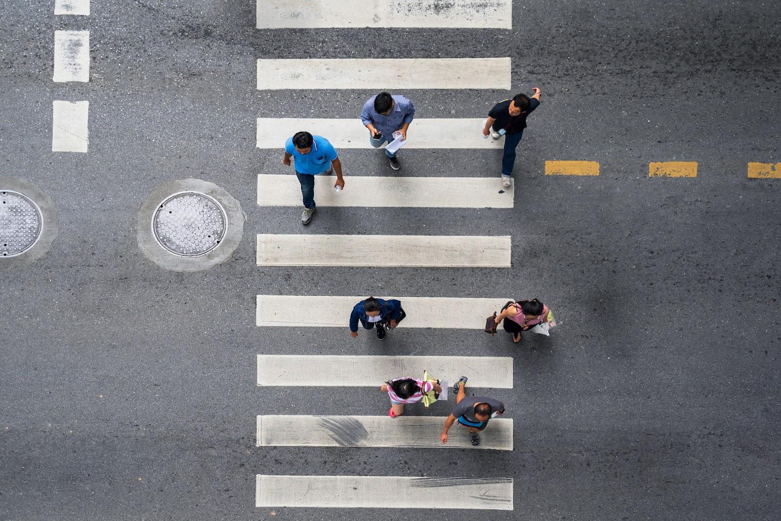 Birds-eye view of pedestrians following crosswalk markings at an intersection.
