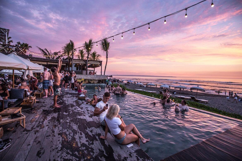 أشخاص يجلسون عند مسبح خارجي مطل على الشاطئ في بالي
