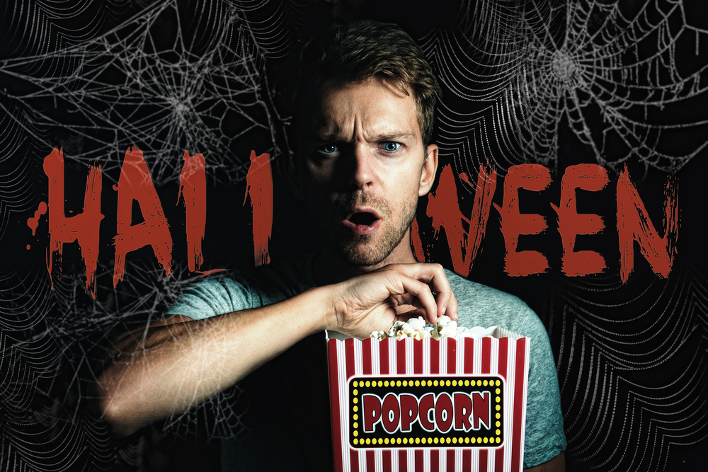 spiderweb on a black background with the word Halloween in Orange superimposed a man eating popcorn with a terrified expression on his face