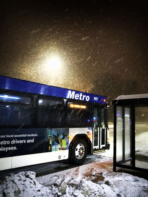Metro Bus at a bus stop on a snowy night