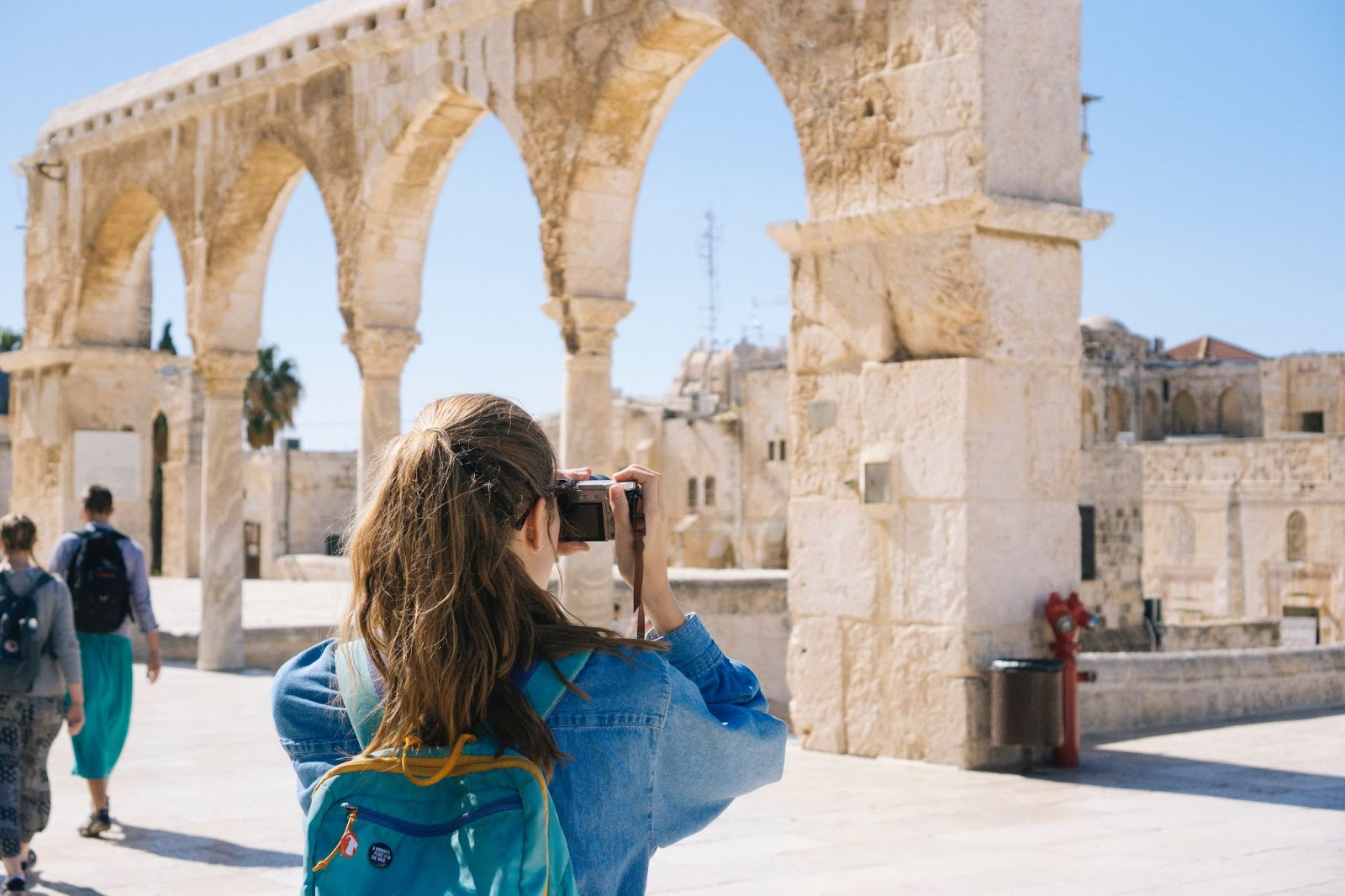 Picture of a female tourist taking a picture with her camera. This is concerning an article on how to insure camera equipment when traveling abroad.