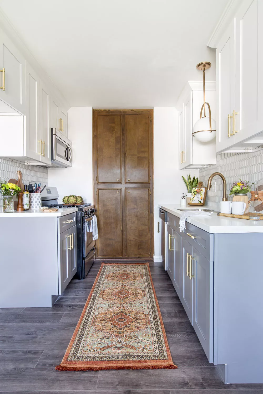 white galley kitchen with grey shaker base cabinets white wall cabinets gold hardware large rug