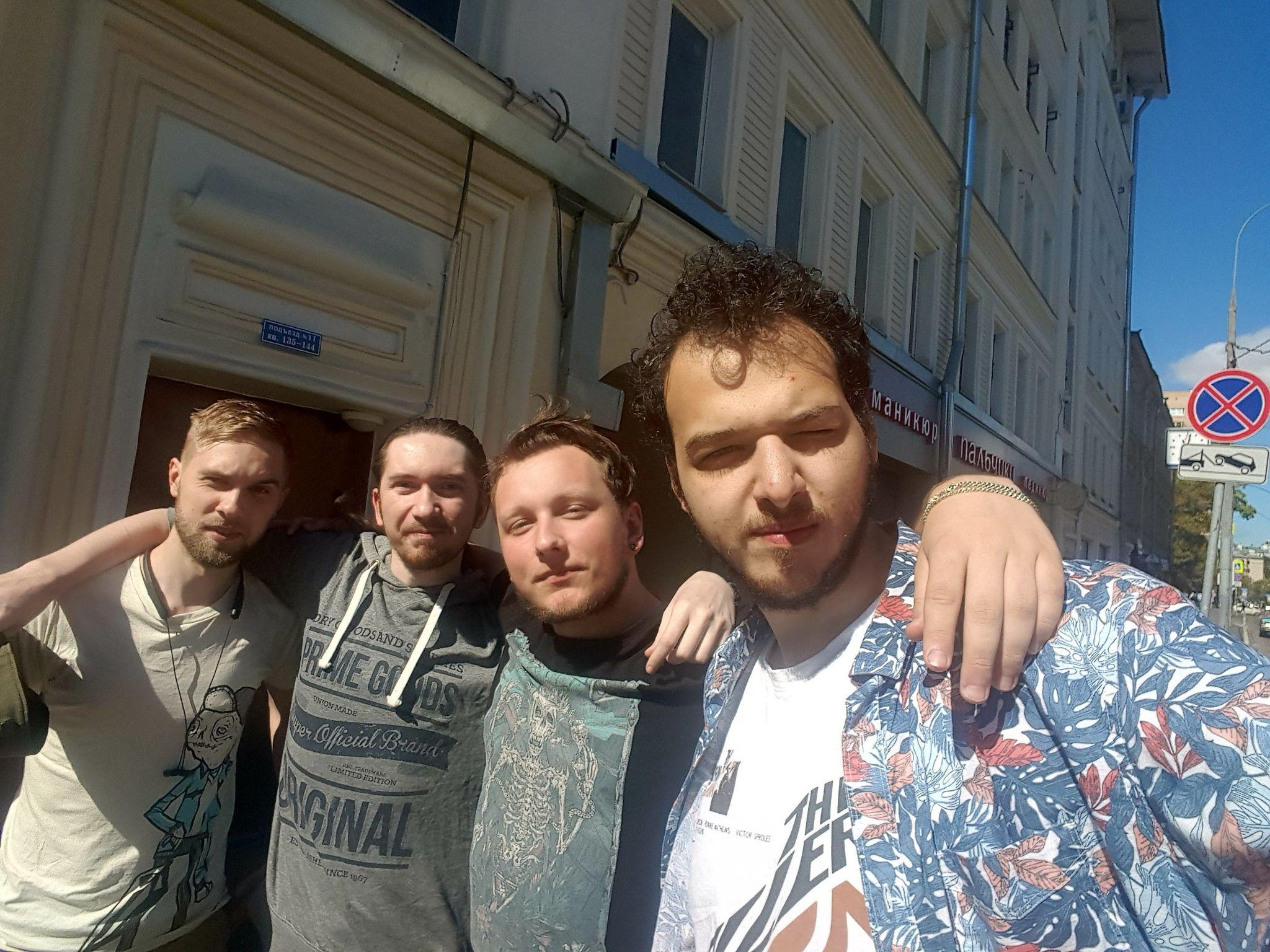 Four individuals pose for a picture together outside near a building.