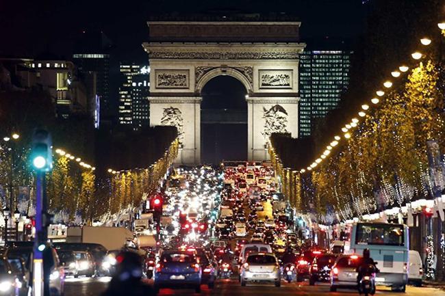 Hàng trăm bóng đèn điện treo trên hàng cây chạy dọc đại lộ Champs Elysees tới đường Arc de Triomphe ở Paris.