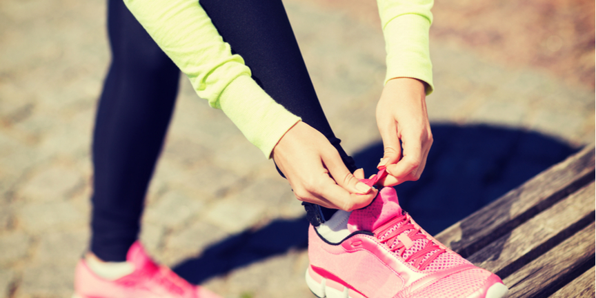 woman-in-fluorescent-top-and-black-leggings-laces-up-pink-running-shoes