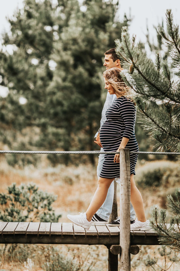 Man and pregnant woman walking hand in hand among pine trees.