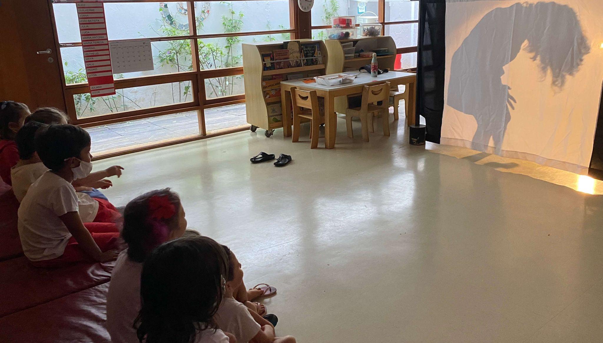 A imagem mostra um teatro de sombras e uma plateia com algumas crianças.