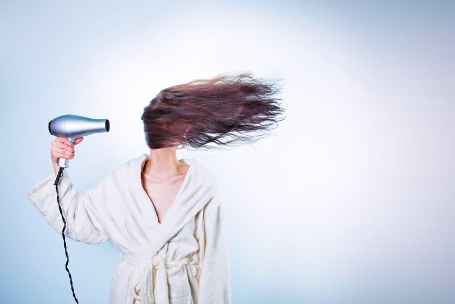 Woman Holding Gray Hair Dryer and Wearing White Bathrobe