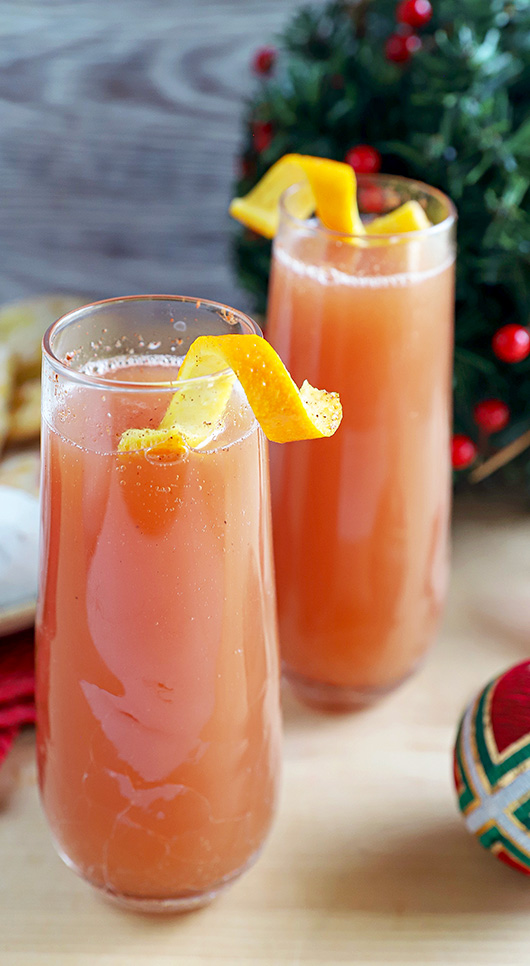 2 sparkling apple cranberry mimosa mocktails in stemless champagne flutes with orange twists