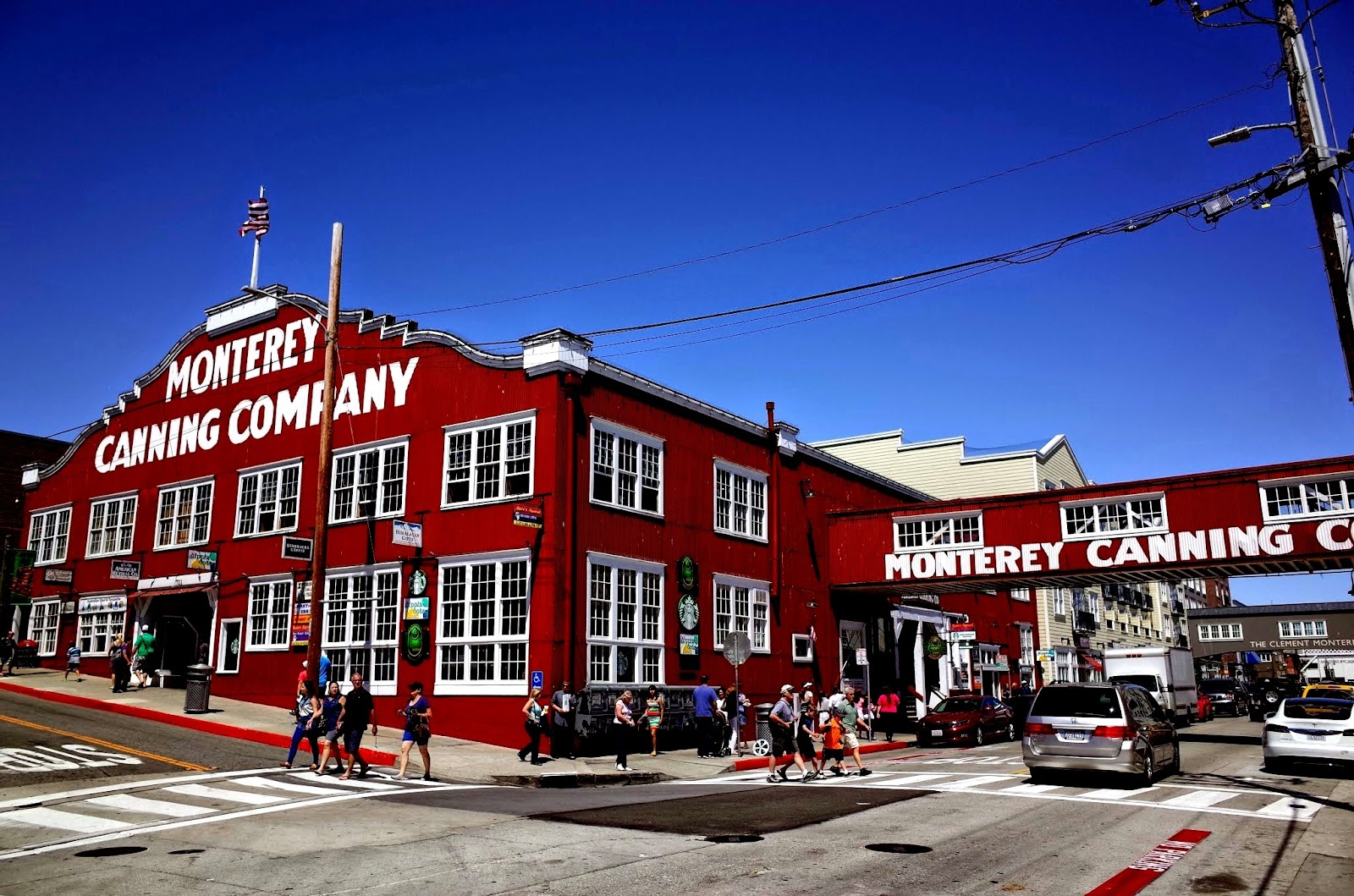 monterey canning company big red building and two pedestrian crossings with people on a clear summer day in california