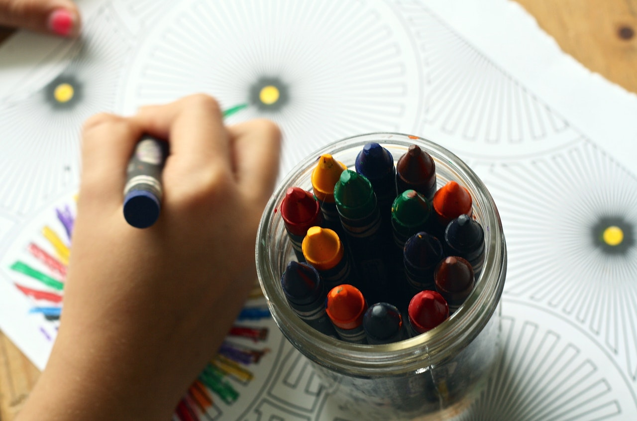 A child colors in a coloring page with crayons from a glass jar.