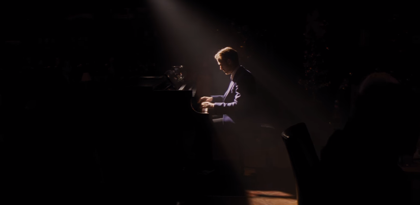 Ryan Gosling as Seb in La La Land. Seb is seated at a piano with a spotlight illuminating his silhouette in the darkness.