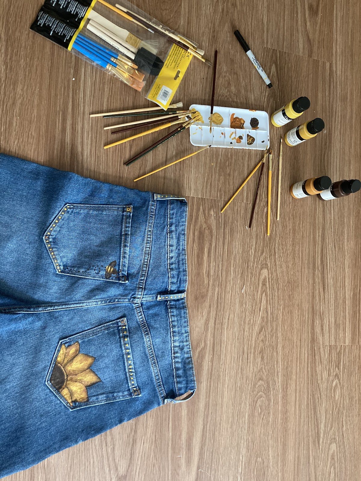 Photo of jeans with sunflowers painted on the back pockets. Yellow, orange, and brown paint bottles with paint brushes and painter palletlay next to the jeans.
