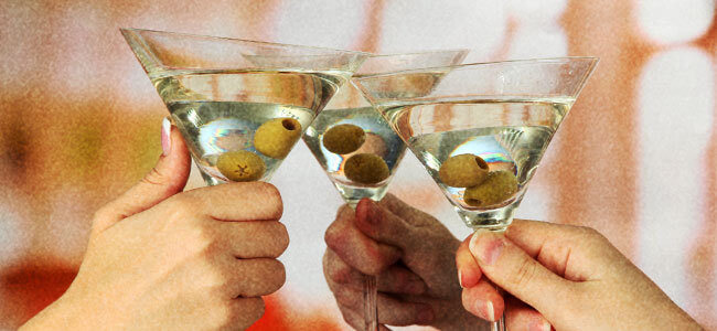 Three martini glasses clinking together in a toast.