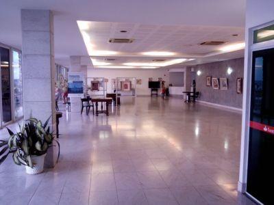 Salão de exposição, ambiente amplo com janelas que ocupam toda a parede, limpo e organizado