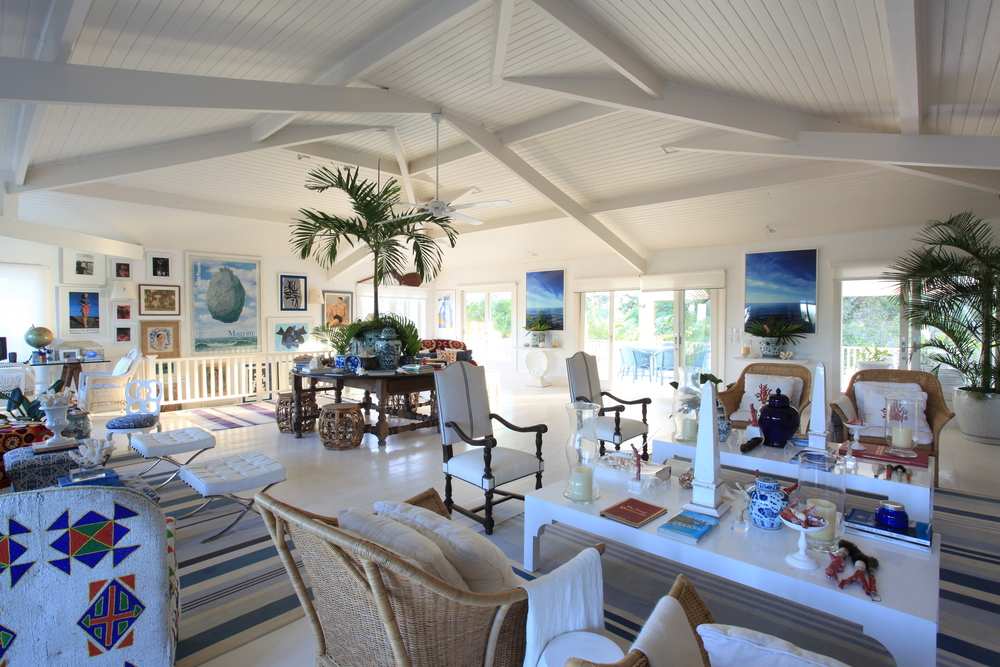 Ambiente branco, mesas e poltronas, plantas e quadros.