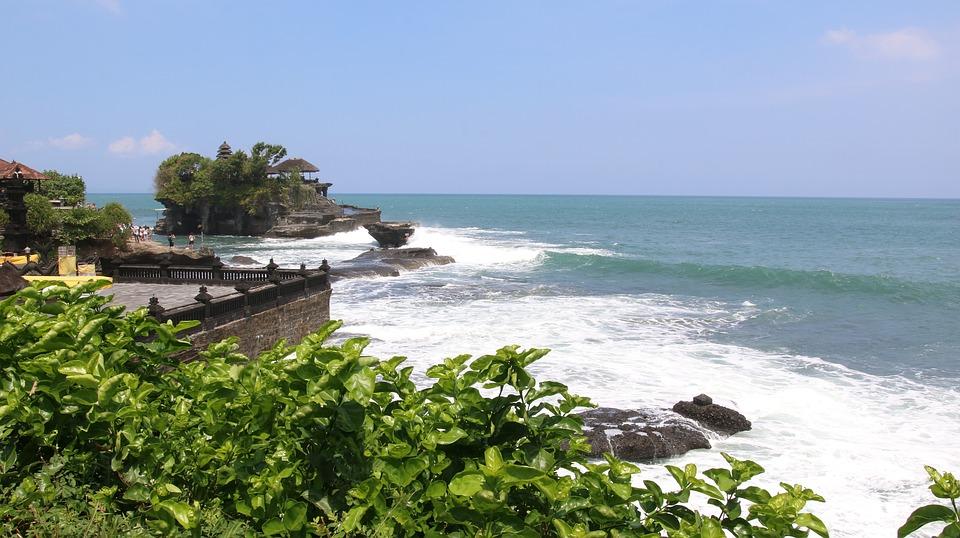 Surf breaking on a rocky coast near Bali.