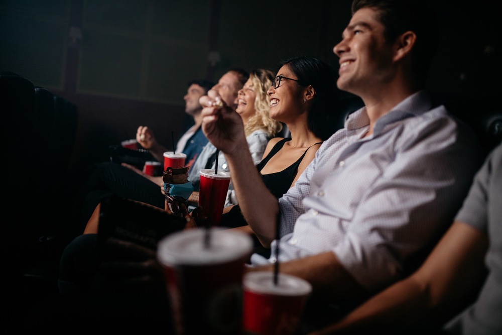 Group of people in theater with popcorn and drinks.