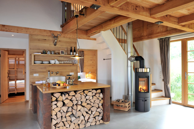 rustic wood cabin with miniature kitchen in the center of the home. wood open shelving and a wooden center island tie the kitchen in with the rest of the home's finishes
