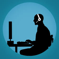 Silhouette of person talking into headset and looking at computer screen