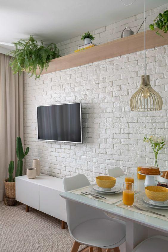 Sala com plantas, mesa de jantar posta branca, rack branco e TV.