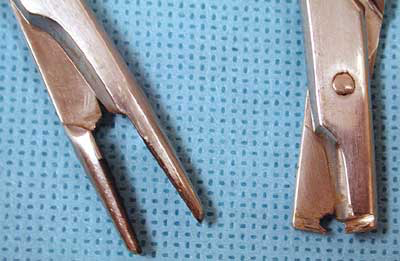 The flat grind wheel on a hand-held rotary tool can be used to remove the needle holder's tips and make cuts