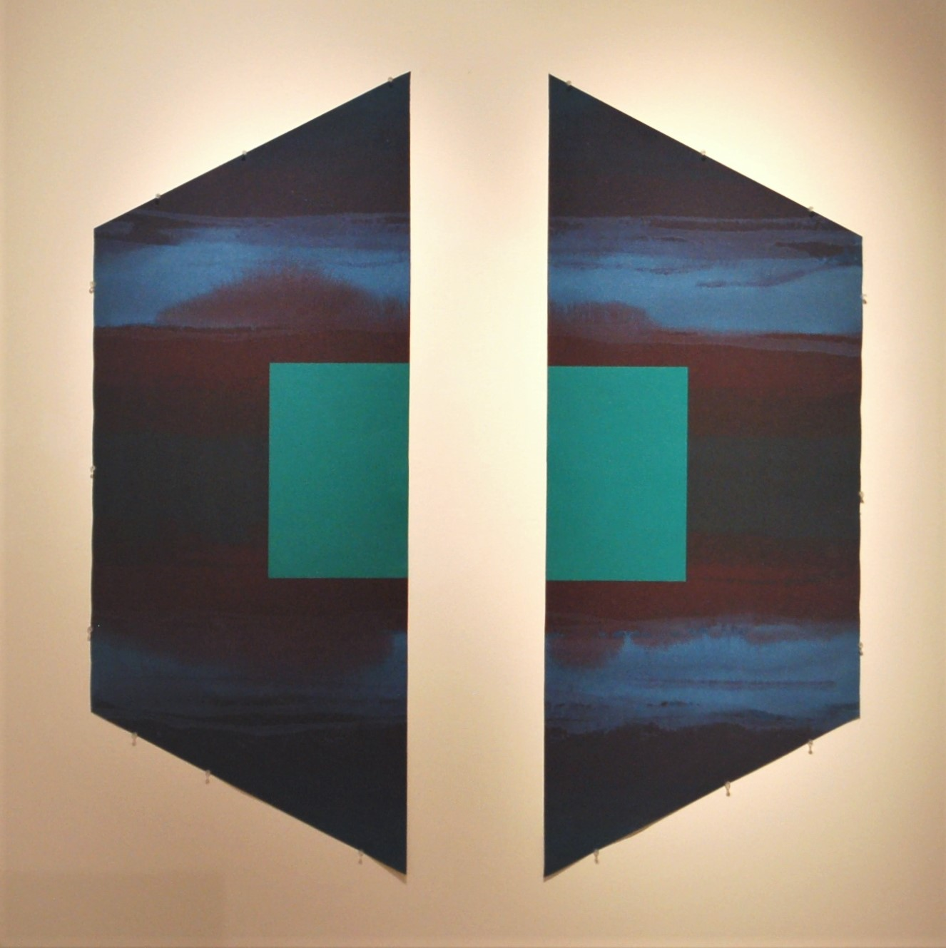 A hexagonal painting cut in half, each side is symmetrical with a teal square in the middle and a blue background.