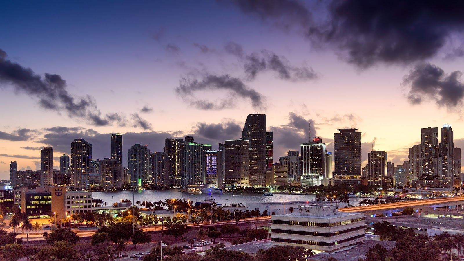 miami beach skyscrapers city skyline and water in foreground during colorful sunset in florida. See this coastal city during a Florida road trip