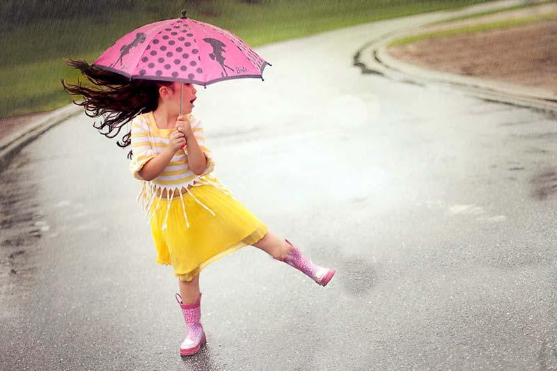 A child holding an umbrella in the rain.