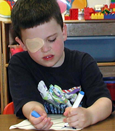 Child with patch to help correct lazy eye or amblyopia