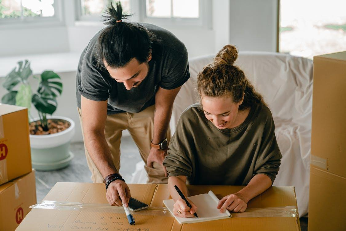 Cheerful diverse couple writing in notebook near boxes before relocation