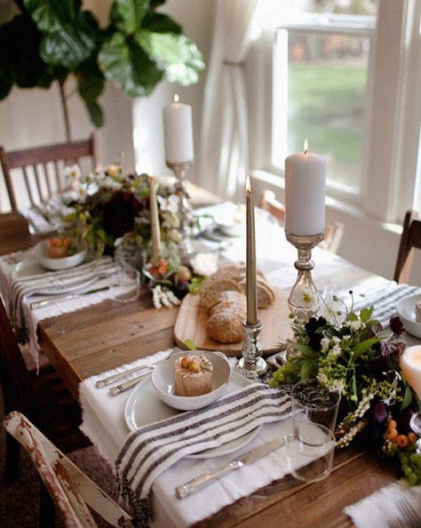small tablescape for thanksgiving or fall dinner with assorted plants and flowers, candles, rustic chairs and table