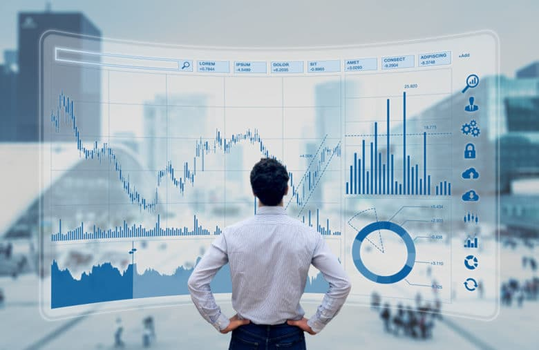 Photo d'un trader devant un dashboard boursier qui présente de multiples indicateurs