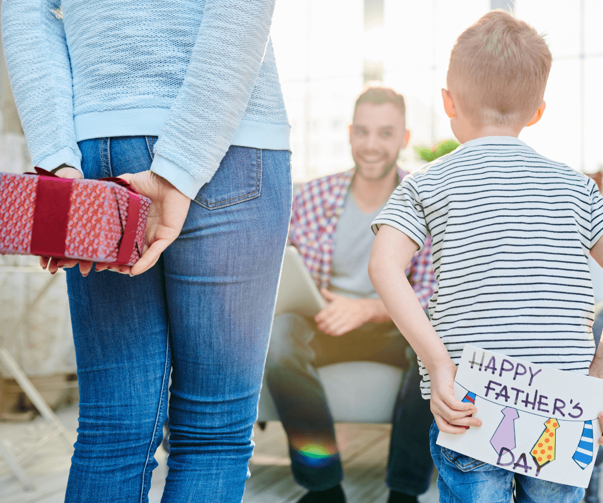 Mother and son facing dad while holding presents behind their back.