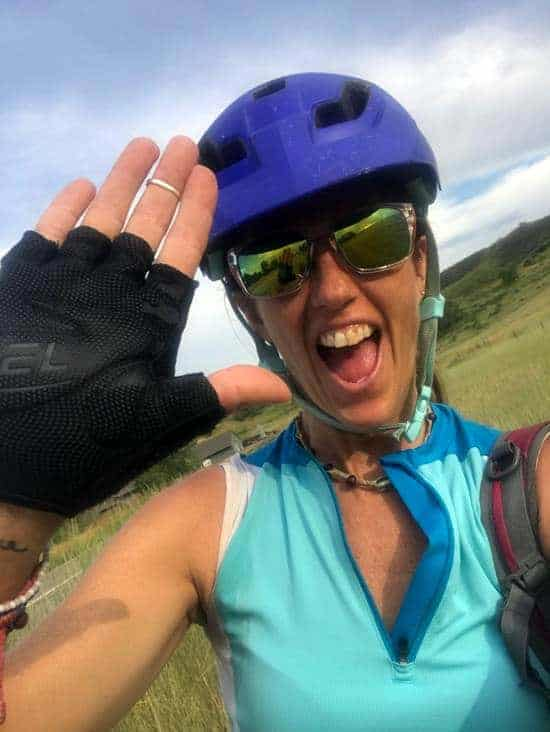 April offering a high five to the camera while in biking gear