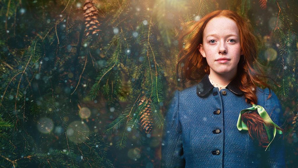 Mulher branca com cabelos ruivos compridos presos em trança veste um casaco azul fechado está do lado direito da imagem. Do lado esquerdo é possível ver plantas verdes e marrons e uma luz no topo da foto. Foto: Reprodução Netflix.